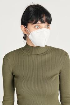 Maqueta de máscara facial en una mujer con un top de cuello alto verde