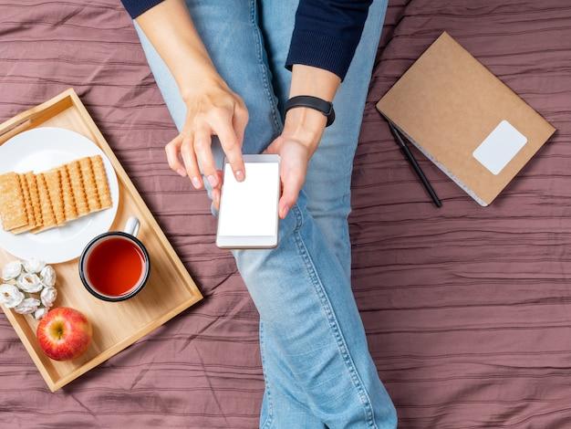Maqueta con mujer con teléfono inteligente, tocando la pantalla, muebles para el hogar, cama, acostado