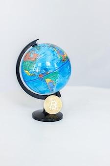 Una maqueta del mundo y bitcoin sobre un fondo blanco.