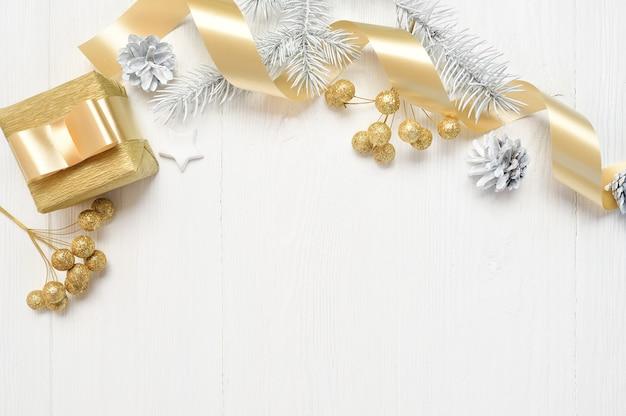 Maqueta de navidad árbol blanco, lazo beige, caja de regalo dorada y cono.