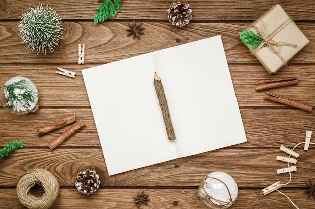 Maqueta de navidad cuaderno en blanco sobre madera