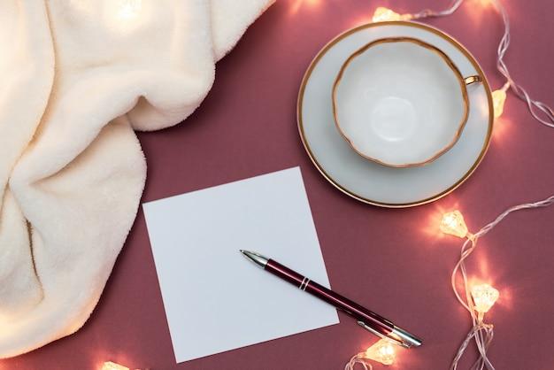Maqueta de navidad con papel blanco, taza blanca vacía y guirnalda de navidad