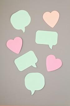 Maqueta con notas adhesivas en forma de burbujas de discurso y corazones con espacio de copia