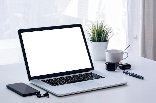 Maqueta de ordenador portátil con pantalla de balnk y gadget en mesa blanca con fondo claro brillante.