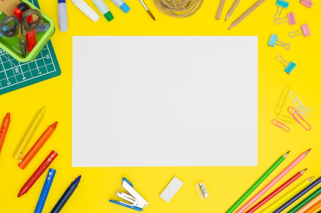 Maqueta de página de papel en blanco sobre tabla amarilla con herramientas de office. copia espacio