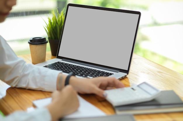 Maqueta de la pantalla del portátil portátil en pantalla en blanco en el escritorio mientras la mujer trabaja en la calculadora financiera