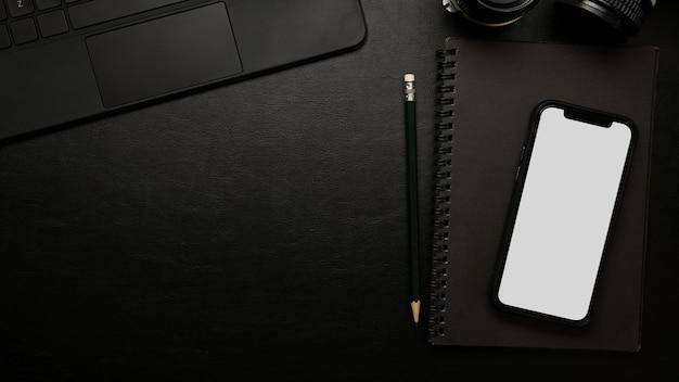 Maqueta de la pantalla del teléfono inteligente de la mesa de estudio oscura moderna de la vista superior del primer en superficie negra
