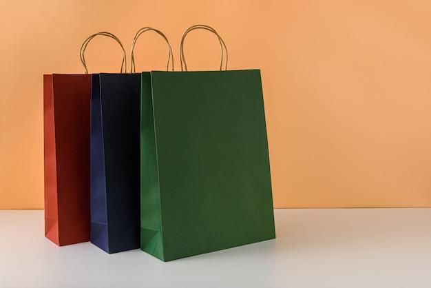 Maqueta de paquete de artesanía en blanco o bolsa de papel de colores con asas