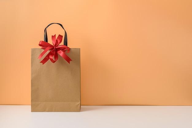 Maqueta de paquete de artesanía en blanco o bolsa de papel marrón con lazo y asas de cinta roja