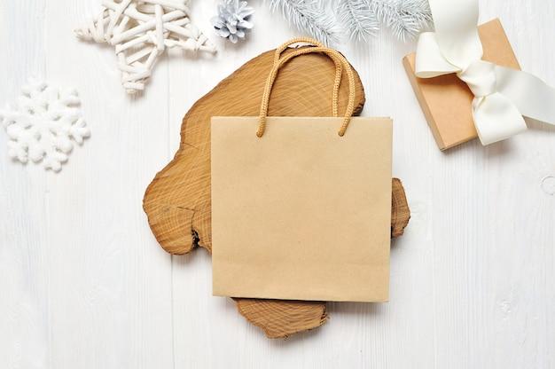 Maqueta de paquete de artesanía de navidad y regalo, flatlay sobre un fondo blanco de madera