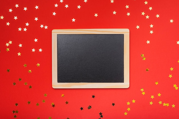 Maqueta de pizarra con fondo rojo y estrellas doradas