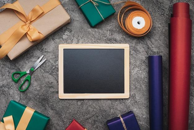 Maqueta de pizarra sobre fondo texturizado con regalos y papel de regalo