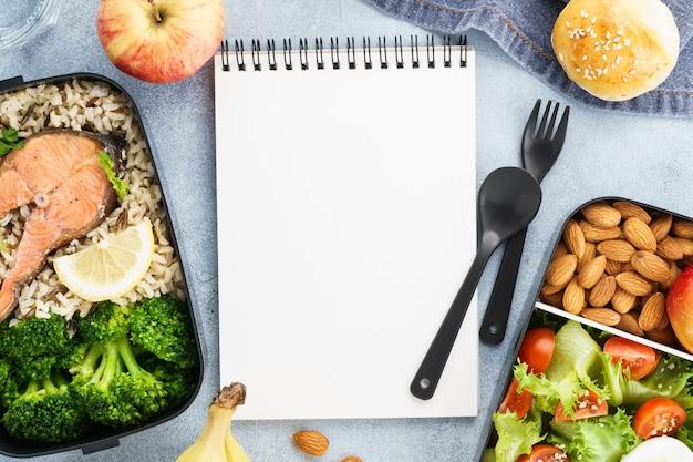 Maqueta de plan de dieta con loncheras saludables y bloc de notas vacío.