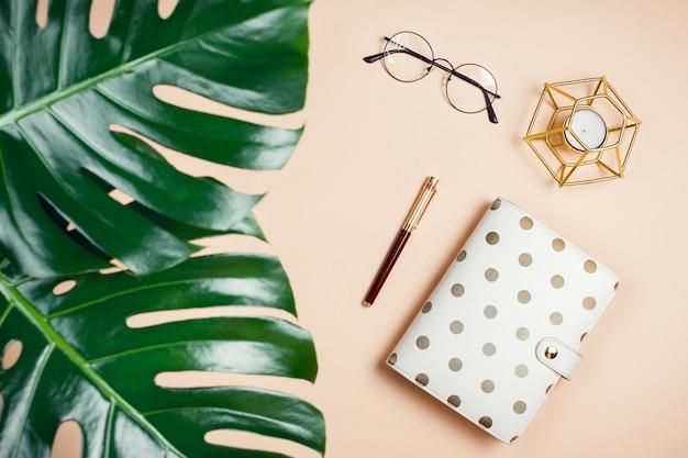 Maqueta plana de negocios con hojas de filodendro monstera, agenda, velas y vasos