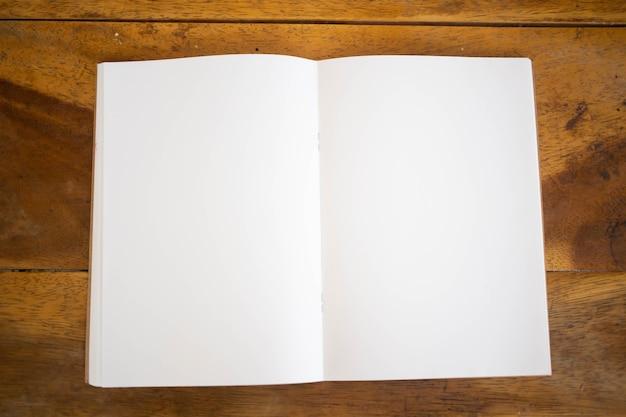 Maqueta de portada de libro en blanco sobre fondo de madera.