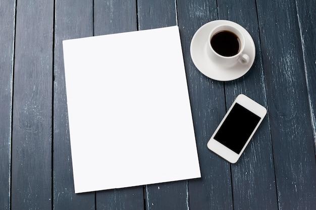 Maqueta de portada de revista o catálogo en blanco, con taza de café y teléfono inteligente
