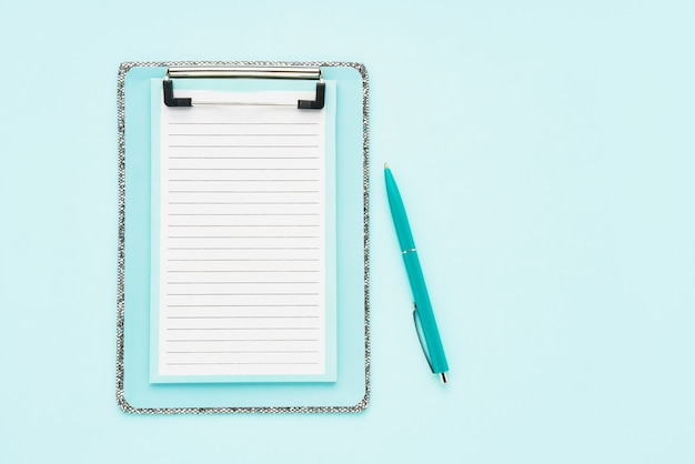 Maqueta de portapapeles en blanco y bolígrafo sobre fondo azul claro.