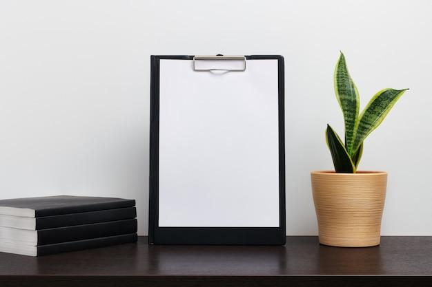 Maqueta de portapapeles negro con cactus en una olla y libro sobre la mesa de espacio de trabajo oscuro y fondo blanco