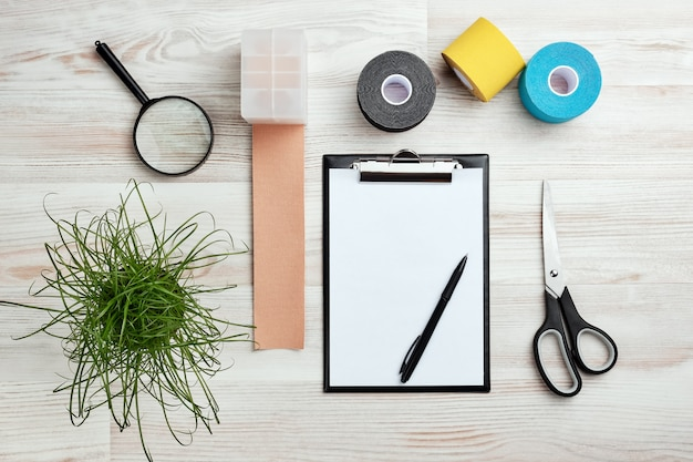 Maqueta con portapapeles, rollos de cinta kinesio de colores, tijeras y otras herramientas