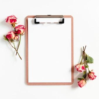 Maqueta de portapapeles y rosas rosadas sobre un fondo blanco