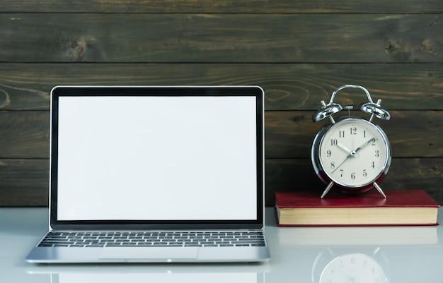 Maqueta portátil y despertador con fondo de madera en la mesa de trabajo