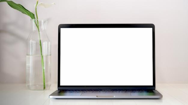 Maqueta portátil en el espacio de trabajo de madera blanca.