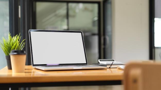 Maqueta de portátil con material de oficina y cosas sobre la mesa de madera con el interior de la oficina en segundo plano.