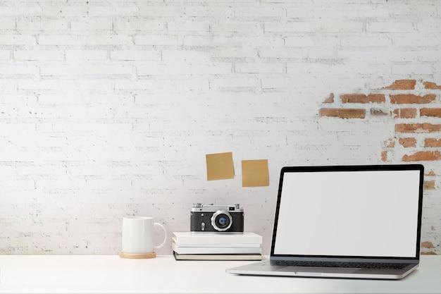 Maqueta portátil de pantalla en blanco con pared de ladrillo blanco