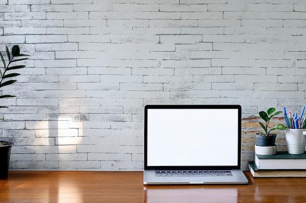 Maqueta portátil con pantalla en blanco, planta de interior y pila de libro sobre la mesa de madera, pantalla en blanco para diseño gráfico.