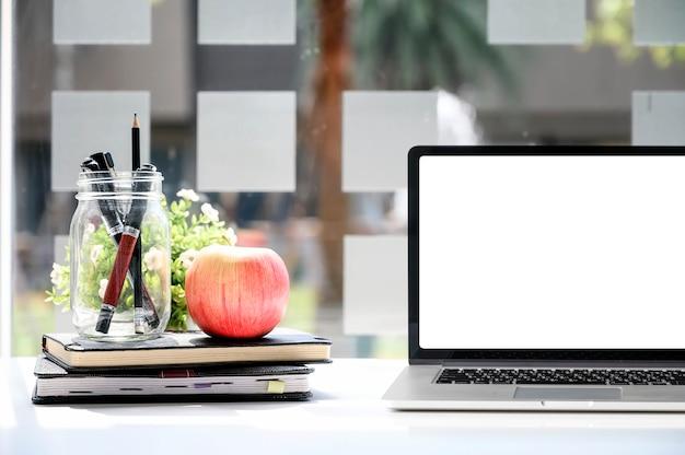 Maqueta portátil con pantalla en blanco y suministros.