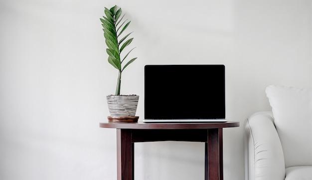 Maqueta portátil de pantalla negra en la mesa de café de madera con sofá de cuero y planta de interior en la sala de estar.