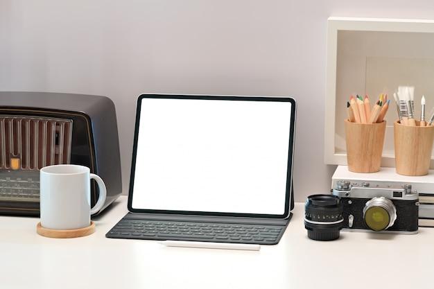 Maqueta portátil, tableta con cámara vintage en mesa de escritorio blanco