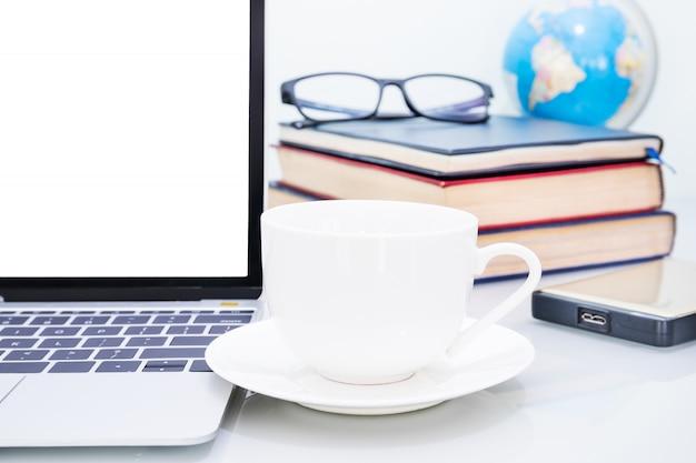 Maqueta portátil y taza de café en la mesa
