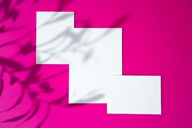 Maqueta publicitaria. businesscards en blanco blanco sobre fondo rosa brillante