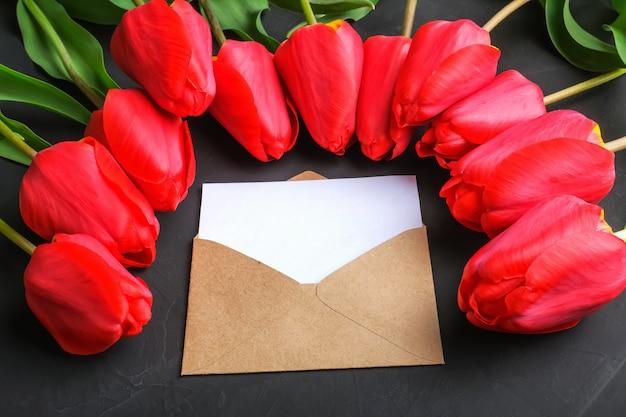 Maqueta del ramo de tulipanes rojos frescos y tarjeta de felicitación en blanco en sobre de kraft