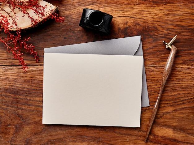 Maqueta de sobres en blanco sobre fondo de madera con pluma y tinta de caligrafía