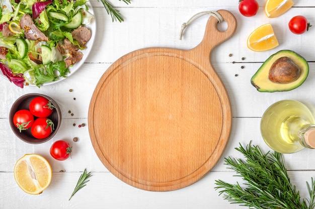 Maqueta con tabla de cortar de madera vacía. ensalada fresca e ingredientes para cocinar sobre fondo blanco de madera.