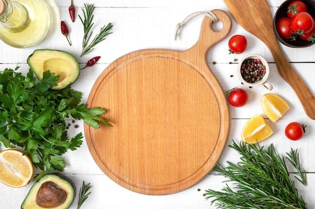 Maqueta con tabla de cortar de madera vacía. verduras frescas e ingredientes para cocinar sobre fondo blanco de madera.