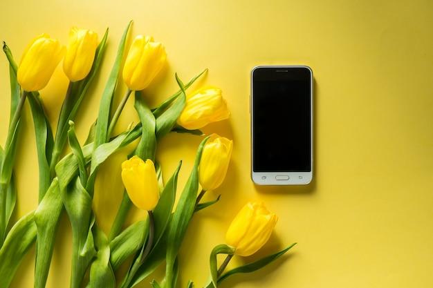 Maqueta de tableta de computadora con ramo de tulipanes en la vista superior sobre fondo amarillo colorido tiro panorámico