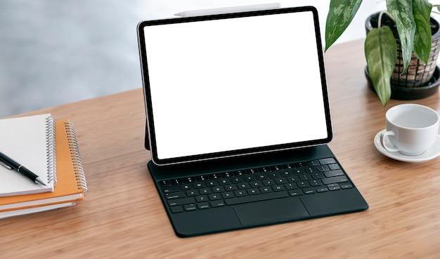 Maqueta de tableta de pantalla en blanco, taza de café y cuaderno sobre mesa de madera.