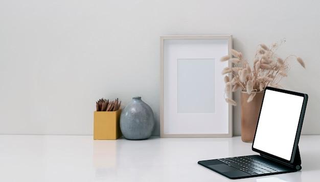 Maqueta de tableta de pantalla en blanco con teclado mágico en la mesa superior blanca.