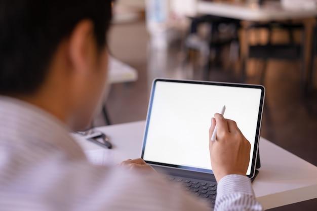 Maqueta tableta de pantalla de escritorio blanco en blanco con un hombre que trabaja. tableta de pantalla blanca para montaje gráfico.