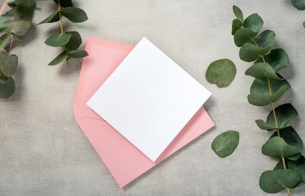 Maqueta de tarjeta de invitación cuadrada de sobre rosa con una rama de eucalipto