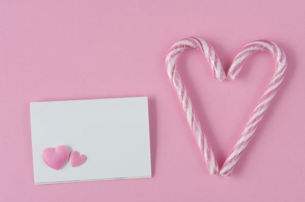 Maqueta de tarjeta de papel sobre fondo rosa con corazones. dos bastones de caramelo haciendo un corazón. vista superior. endecha plana. confesión de amor.