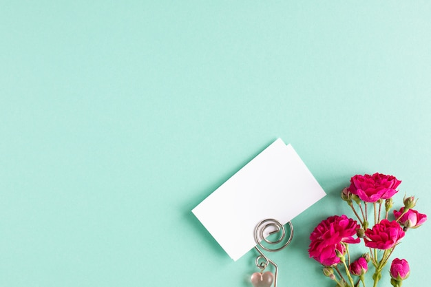 Maqueta de tarjetas de visita sobre un fondo de color y una flor rosa, copyspace, topview.
