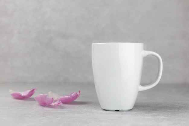 Maqueta de taza blanca en blanco con pétalos de tulipanes rosas, fondo de piedra de hormigón claro. san valentín, madres, composición del día de la mujer.