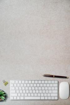 Maqueta teclado blanco con suministros sobre fondo de papel borwn.