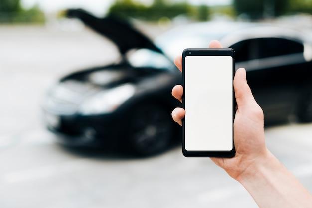 Maqueta de teléfono con coche en segundo plano.