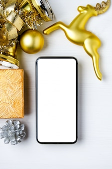 Maqueta de teléfono inteligente con adornos navideños dorados