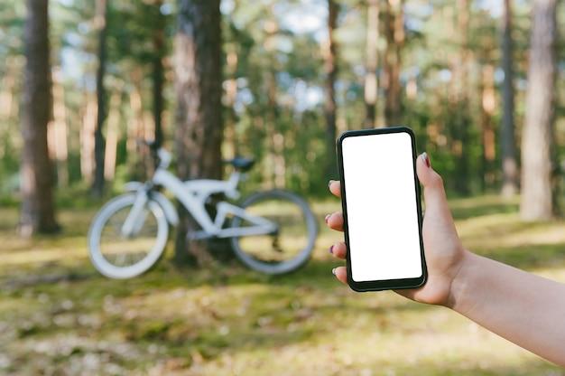 Maqueta de un teléfono inteligente en la mano de una niña. en el contexto de una bicicleta en el bosque.